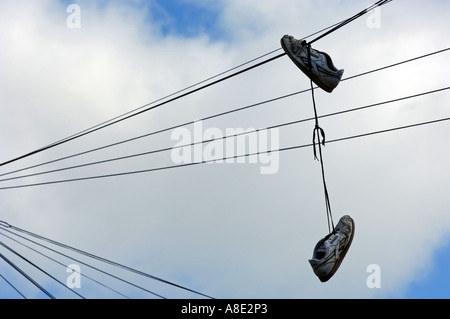 Shoes hanging from telephone wire - Stock Photo
