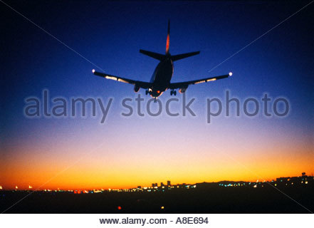 Commercial Airliner landing at Phoenix International Airport at Dusk   tall buildings of Phoenix can be seen in - Stock Photo