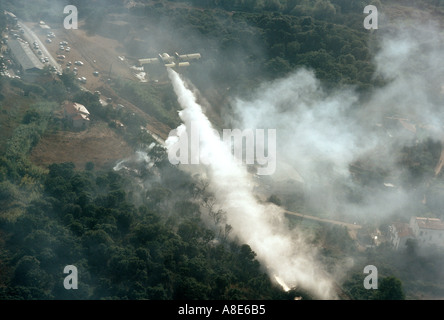 Aerial view of a Canadair firefighting water bomber airplane dousing water over a wildfire threatening houses and - Stock Photo