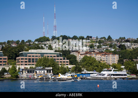 Boats and plans on Lake Washington with radio masts on hill Seattle USA - Stock Photo