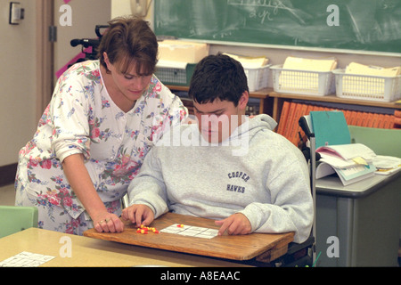 Teacher studying with handicapped student age 35 and 16. New Hope Minnesota USA - Stock Photo