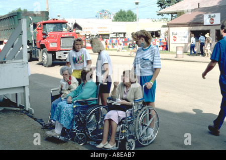 Teens age 15 guiding seniors age 80 in wheelchairs at State Fair. St Paul Minnesota USA - Stock Photo
