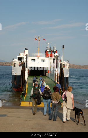Foot passengers embarking onto a small carferry, a ten minute sea crossing to Fionnphort on the Isle of Mull from - Stock Photo