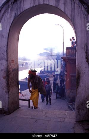 Nepal Sadhu walks past mass ranks of funeral pyres on Shivas birthday - Stock Photo