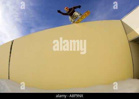 Urban Snowboarder slides a wall - Stock Photo