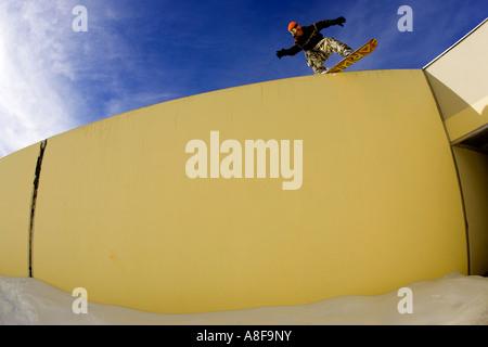 Urban Snowboarder sliding a wall in ski village - Stock Photo