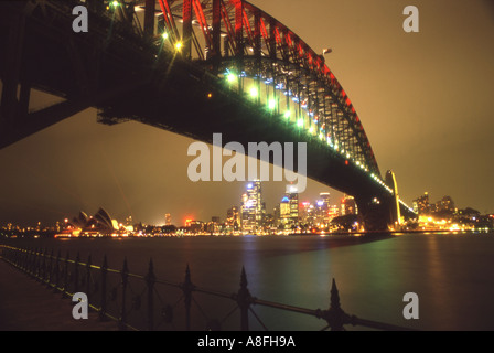 Sydney Harbour Bridge lit up during the Citylights Festival 2004 with Opera House and CBD skyline background - Stock Photo