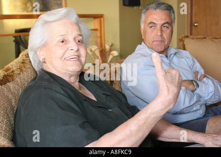 Key Biscayne Florida Hispanic Cuban relatives plan family reunion meeting talking listening male senior female - Stock Photo