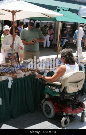 Miami Beach Florida Lincoln Road Mall disabled snack vendor electric wheelchair shoppers - Stock Photo