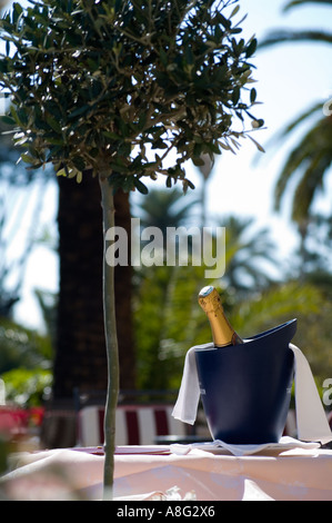 A bottle of Champage in a bucket of ice on an outside table at a restaurant - Stock Photo