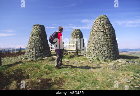 Hill walking walker at The Three Brethren cairns on the Southern Upland Way Scottish Borders Scotland UK - Stock Photo