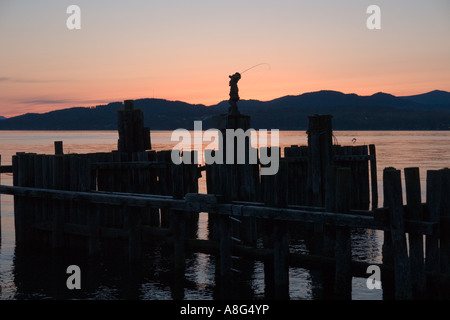 Sculpture of fisherman at sunset over the pier at Davis Bay, British Columbia on the Strait of Georgia - Stock Photo