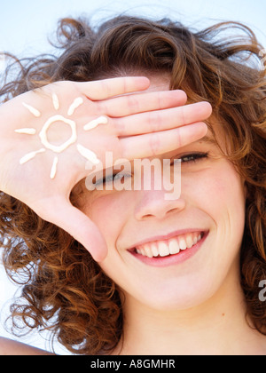 Teenage girl smiling with figure of a sun drawn in suncream on her hand Light skin needs to be protected against - Stock Photo