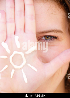 Teenage girls eye and hand closeup with figure of a sun drawn in suncream on her hand - Stock Photo