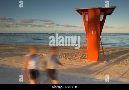 A couple man and woman enjoy an early morning walk along a quiet section of Waikik Beach Oahu USA - Stock Photo