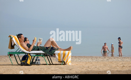 Holidaymakers relaxing on sun loungers whilst reading Family at the shore Beach beside the Red Sea at Nuweiba Sinai - Stock Photo