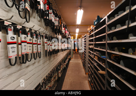 Carparts store warehouse with spare parts for cars with belts cupboard walk path - Stock Photo