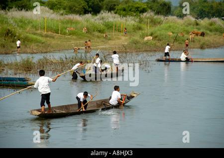 Many boys on boats on Nam Song River Vang Vieng Laos - Stock Photo