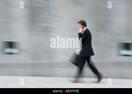 Blurred picture of an huried up business man with executive case in front of an high concrete wall in Munich - Stock Photo
