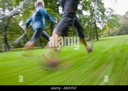 Motion studie of two nordic walker with sticks and sportive clothing walking on a green meadow in the English Garden - Stock Photo