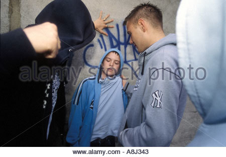 Teenage boy being bullied by gang of youths UK - Stock Photo
