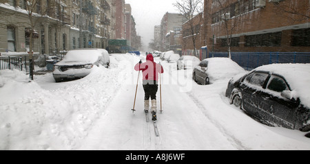 A young woman cross country skis down a snow covered street in Harlem after a blizzard in New York City USA February - Stock Photo