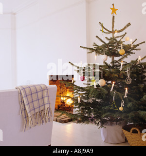 Decorated Christmas tree by open fireplace - Stock Photo