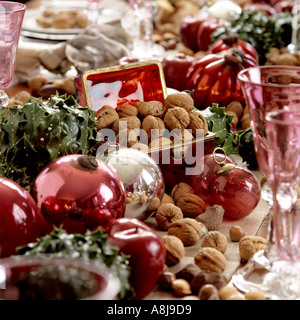 pink baubles, nuts and glassware on a Christmas table - Stock Photo