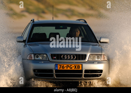 S4 in water action with big wave on the front Audi car silver in the Norhtsee North See North sea on the beach driving - Stock Photo