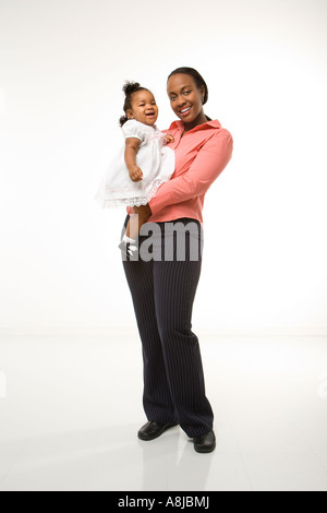 African American woman holding infant girl standing against white background - Stock Photo