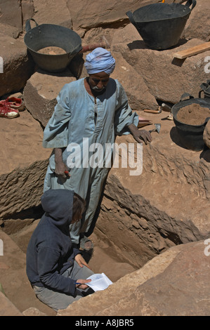 Egyptologist at Luxor Temple with local man excavating a new site - Stock Photo