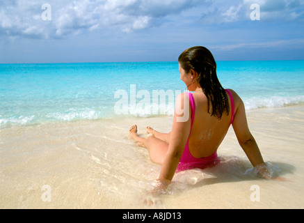 San Salvador back of woman sitting in surf pink suit blue water sky background - Stock Photo