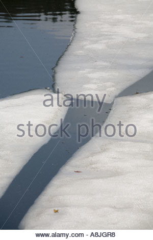 Peaceful lake with breaking ice in late Winter - Stock Photo