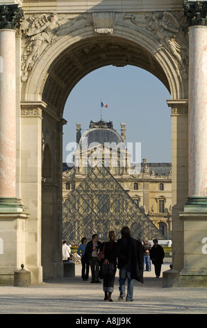 Couple stroll through the Arc de Triomphe du Carrousel with Glass Pyramid and Louvre Museum in the background, Paris, - Stock Photo