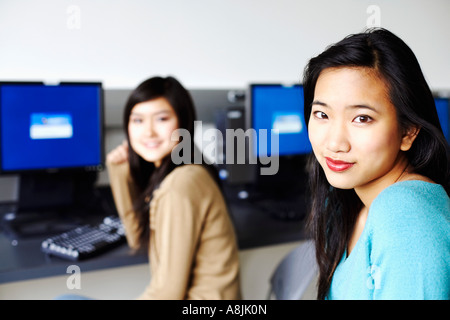 Portrait of two young women sitting in front of computers and smiling - Stock Photo