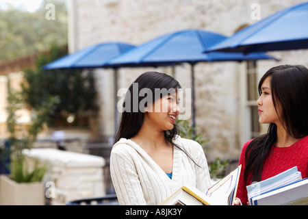 Two young women talking to each other - Stock Photo