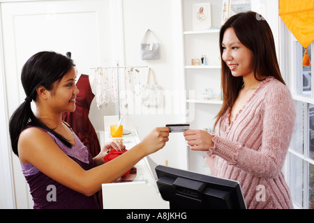 Side profile of a young woman giving a credit card to a sales clerk - Stock Photo