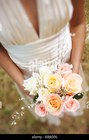 Mid section view of a bride holding a bouquet of flowers - Stock Photo