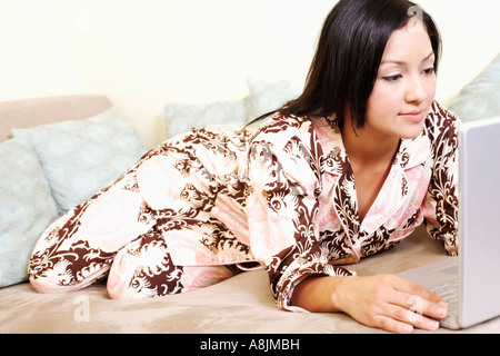 Close-up of a young woman reclining on a couch and using a laptop - Stock Photo