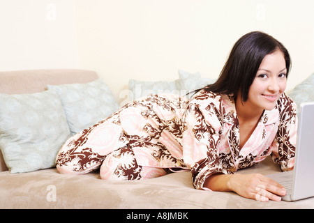 Portrait of a young woman reclining on a couch and using a laptop - Stock Photo