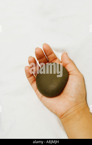 Close-up of a person's hand holding a spa hot stone - Stock Photo