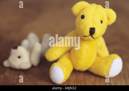 Small yellow teddy bear sitting on a wooden seat or table looking at viewer with a smaller paler ted lying alongside - Stock Photo