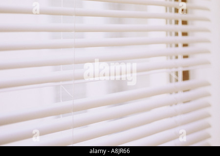 Impressionistic detail of white Venetian blinds down but open with one slat stuck with view of white building opposite - Stock Photo