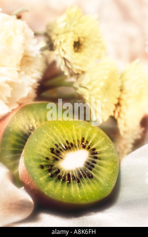 Still life of Kiwi fruit cut in half with background of white flowers - Stock Photo