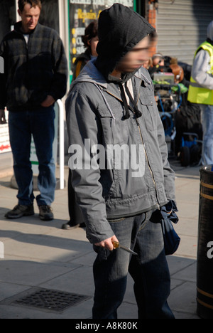 Youth with knife in street. - Stock Photo
