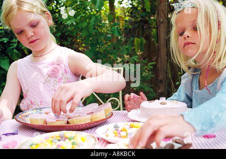 Children decorating cakes - Stock Photo
