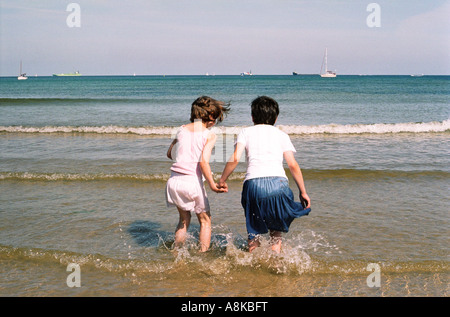 Two children hand in hand jumping waves - Stock Photo