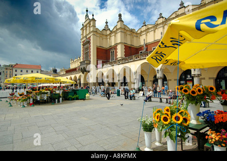 Horizontal wide angle of the 'Cloth Hall' Sukiennice in the centre of the Main Market Square with flower stalls - Stock Photo