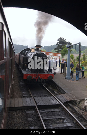 Vertical wide angle of a steam engine and carriages stopped at Weybourne station on the historic Poppy Line. - Stock Photo