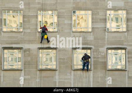 Horizontal portrait of two window cleaners suspended from ropes high up on an office block. - Stock Photo